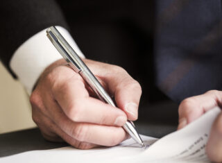 Cropped image of businessman signing document